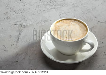 White Cup Of Coffee With Latte Art On Concrete Table