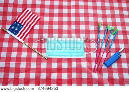 4th of July. Independence Day July 4, 2020 American Flag, Fireworks, Paper Face Mask on a Red and White Checker Board Table Cloth. Covid-19 4th of July preparation. Coronavirus Pandemic Preparation.