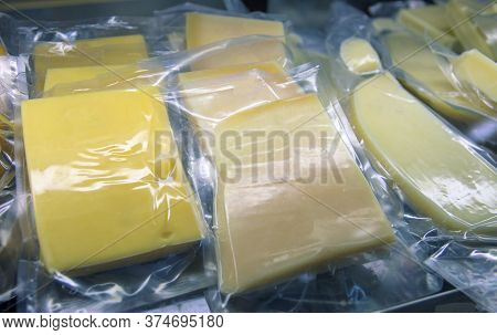 Stock Of Yellow Cheese In Vacuum Packaging. Cheese Slices In Grocery Shop. Fresh Goat Cheese For Sal