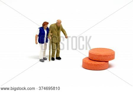 Miniature Elderly Couple And Pills On White Background. Nurse Helping Old Man. Hospitalization And M