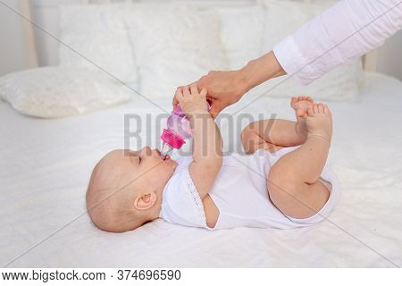 A 6-month-old Baby Lies On A White Bed And Drinks Milk From A Bottle, Baby Food Concept, Text Space