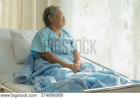 Lonely Asian Elderly Female Patient Lying On The Bed In The Hospital And Looking Away Outside The Wi