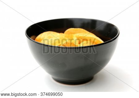 Black Ceramic Bowl filled with Potato Chips. Potato Chips are enjoyed world wide. Isolated on white. Room for text.