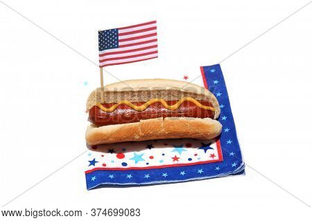 Hot Dog. Hot Dog with an American Flag on a Patriotic Napkin. Isolated on white. Room for text. Holiday Picnic Food. Hot Dogs are the Perfect Holiday and Picnic Food for the 4th of July.