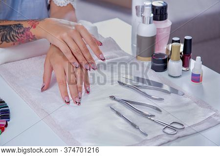 Well-groomed Womens Hands With A New Manicure On The Table Near The Decomposed Tools For Manicure.