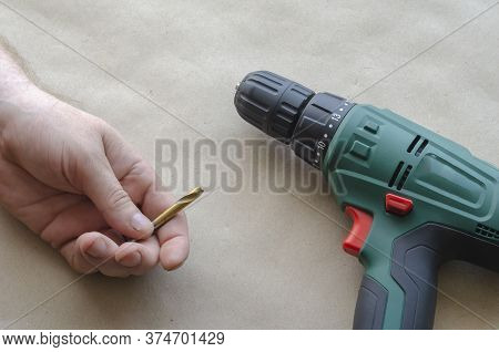 Mans Hand Holds A Broken Drill For Metal. An Electric Drill Lies Nearby. Inept Use Of A Hand-held Po
