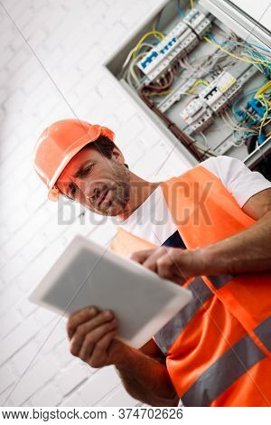 Focus Of Handsome Workman In Safety Vest And Helmet Using Digital Tablet Near Electric Box