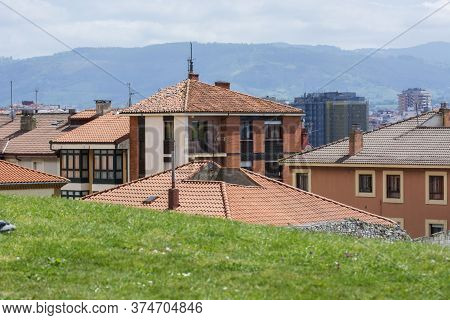 Photo Of Several Roofs With Building Facade, Green Grass And Sunlight.