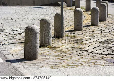 Several Stone Bollards With (sun And Shadow), Grey Ground And Sunlight.