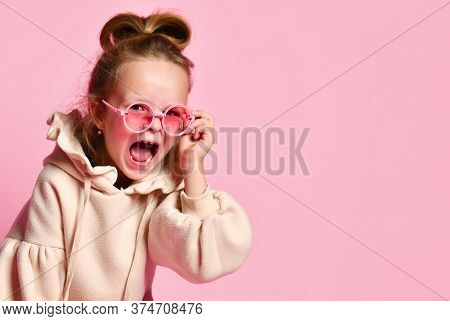 Naughty Girl With Tall Hair Dressed In Pink Hoodie Yelling Angrily Resettling Spectacles On Face. Cl