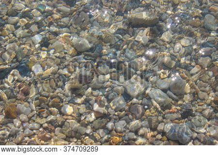 Close-up View Of Multicolored Pebble Of Sea Beach Under Clear Water. Pattern Of Sea Stone Texture Un