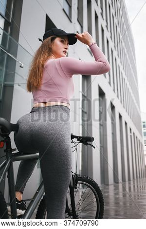 Serious Young Woman With A Sexy Figure On A Bicycle