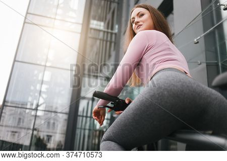 Athletic Young Woman With A Sexy Figure On A Bicycle