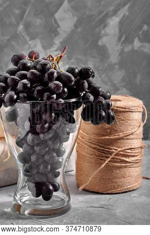 Bunches Of Fresh Ripe Red Grapes On A Concrete Textural Surface. Branch Of Pink Grapes. Red Wine Gra