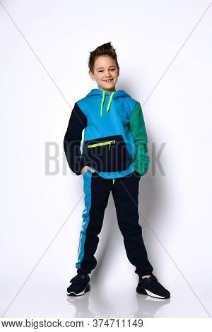 Sly Active Smiling Baby In A Modern Cotton Tracksuit With A Cute Haircut, Hands In Pockets. Stylish
