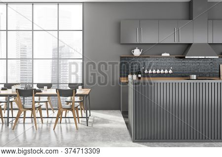Interior Of Modern Kitchen With Gray Walls, Concrete Floor, Gray And Wooden Island And Long Dining T