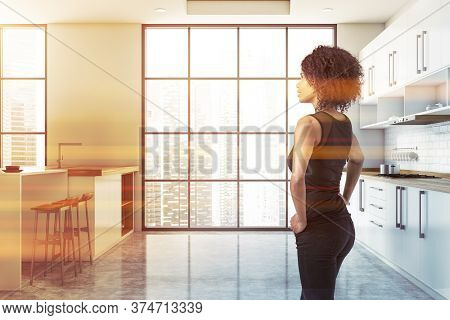 Beautiful Young African American Woman Standing In Luxury Kitchen With White Walls, White Countertop