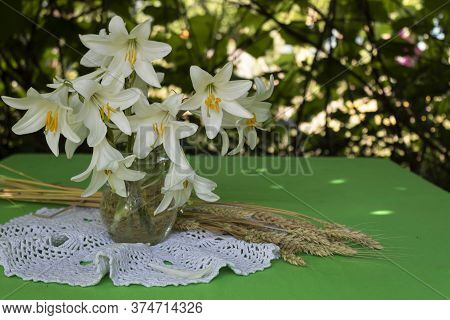 On The Table In The Summerhouse There Is A Bouquet Of White Lilies And Ears Of Wheat.