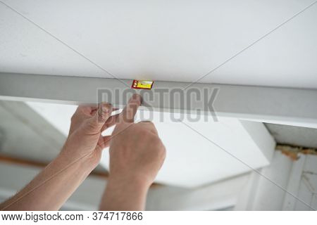 Tool level in men's hands and a flat horizontal surface of the ceiling. Styrofoam, seiling mounting. A man checks a foam ceiling level. Ceiling insulation. Warming. Repair in the house. DIY repair