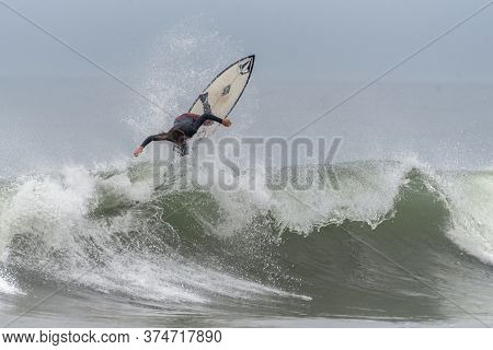 Young Male Surfer Throws Up Spray And Launches Straight Up Above The Face Of A Breaking Wave At Surf