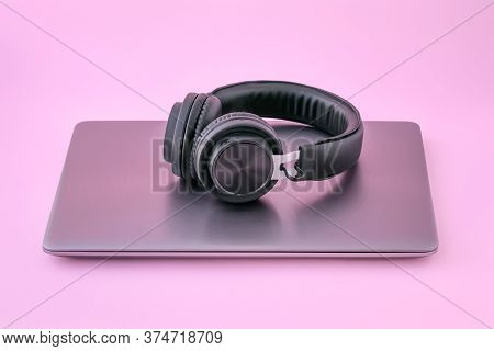 Metal Laptop And Black Headphones On A Pink Background. Closed Notebook With Earphones. The Concept