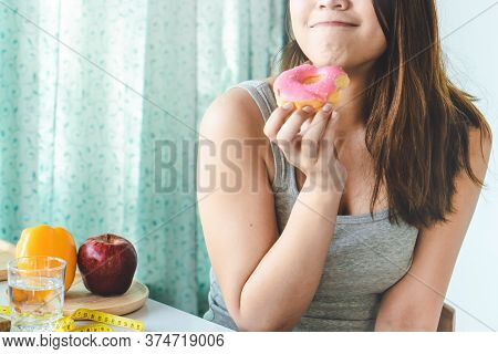 Woman Cheating During Diet And Eating Doughnut. Selective Focus On Mouth.
