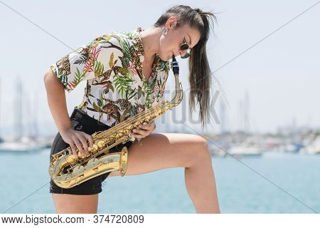 Side View Of A Beautiful Woman Wearing Glasses Playing A Golden Saxophone Outdoors On An Out Of Focu