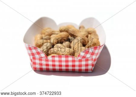 Peanuts. Dry Roasted Salted Peanuts. Fresh Peanuts in shell in a paper basket. Isolated on white. Room for text. Peanuts are loved by People and Animals world wide.