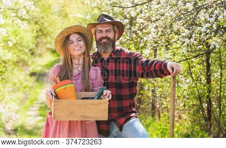 Spring Garden In Blossom. Happy Family In Garden. Couple Of Gardeners. Sexy Woman And Bearded Man Ho
