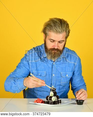 Man Eating Traditional Japanese Food With Chopsticks. Dinner At Home. Hipster Eat Sushi With Chopsti