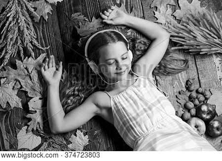 Enjoy Perfect Sound. Girl Lay Fallen Leaves Wooden Background. Music Application For Youth Modern Ga