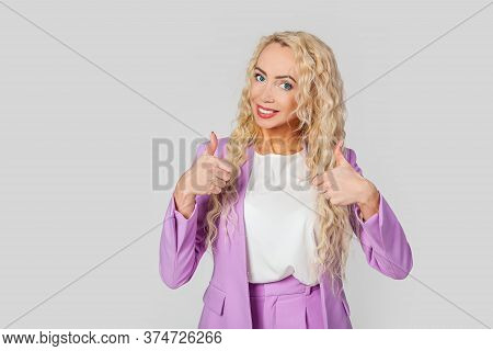 Good Job Dude, Like It. A Pleasant Beautiful Happy Blond Woman, Shows Thumb Up And Smiles Broadly, G