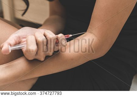 Close Up Pills And Syringe On The Bed.  Depressed Woman Suicide By Using Drug Overdose.