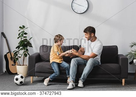 Father And Son Jokingly Fighting On Sofa Near Potted Plants, Soccer Ball And Guitar