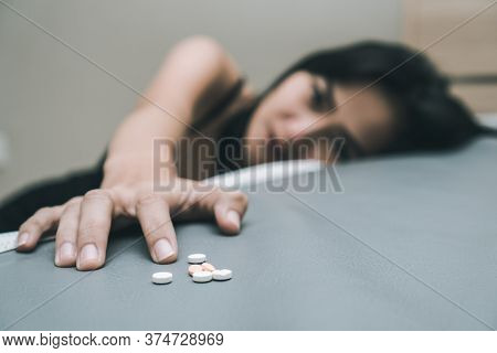 Close Up Pills In Young Women Hands. Stressed Female Taking Drug Overdose Sitting Beside The Bed Try