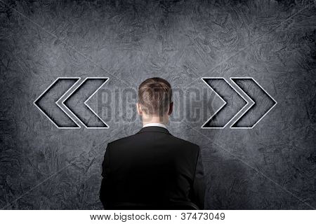 Businessman is standing in front of two direction signs. poster