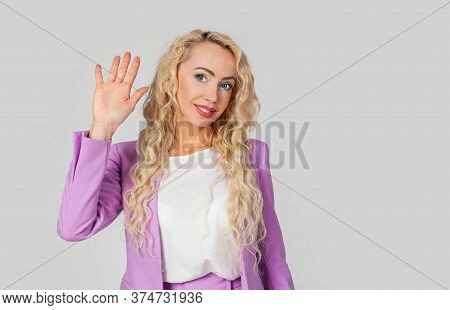 A Woman Raises Her Hand In A Hello Greeting, Waves To You With A Raised Hand. Beautiful Woman Standi