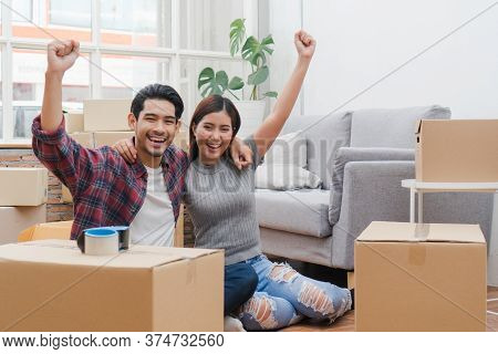 New House / Home Moving And Relocation Concept. Happy Asian New Married Couple Looking At Each Other