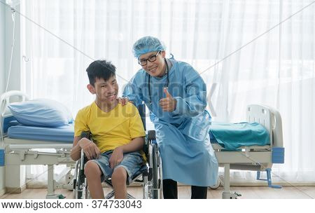Asian Volunteer Doctors Caring And Helping Rehabilitation Of Disabled Boys Stay At The Hospital. The