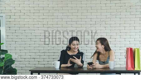 Two Asian Women Who Are Laughing And Attractive Are Friends, Talking About Coffee In A Coffee Shop.