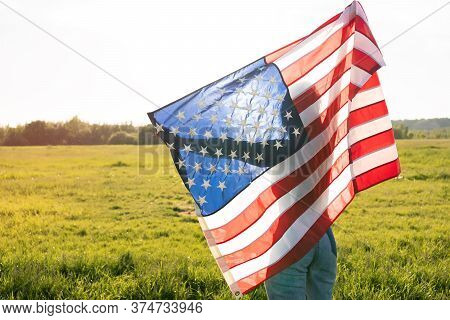 A Silhouette Patriotic Woman Enjoying In Park Field Holding Usa Flag Above Head During Sunset. Ameri