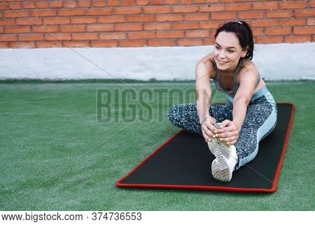 Yoga Girl In Head To Knee Forward Bend Pose. Smiling Woman Is Stretching Legs On Mat After Training