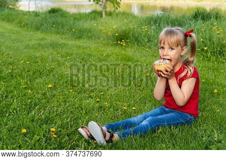 Happy Canada Day Outdoor Celebration. Pretty Cute Caucasian Girl Sitting On Grass And Eating Donut W