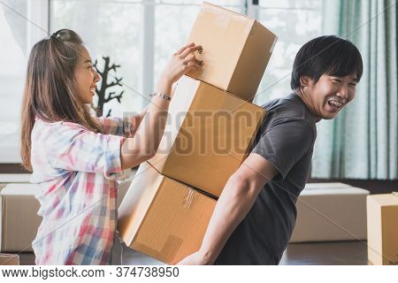 Concept Young Couple Moving House. Asian Woman Helping Man Carry Cardboard Box To Move In New House.