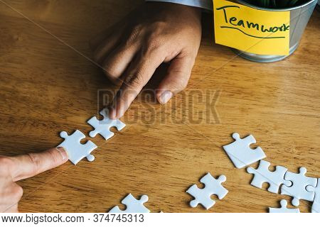 Teamwork, Partners, Connection Concept. Hands Of Two Businessmen Merging Jigsaw Puzzle On The Workin