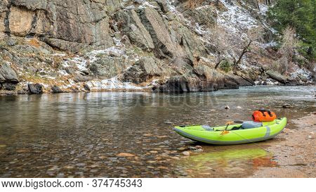 inflatable whitewater kayak with a paddle and dry bag on a rocky shore of a mountain river, early spring scenery - Poudre RIver at Picnic Rock above Fort Collins, Colorado