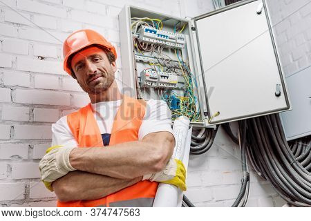 Workman In Helmet And Safety Vest Holding Blueprint And Looking At Camera Near Electric Panel