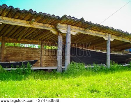 Antique Arbor Made Of Natural Wood For Storing Boats On The Shore In The Summer On A Background Of G