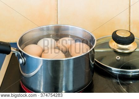 Eggs Boiling In Stainless Steel Saucepan In Home Kitchen