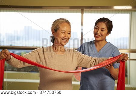Happy Senior Asian Woman Exercising Using Resistance Band Guided By Physical Therapist In Rehab Cent